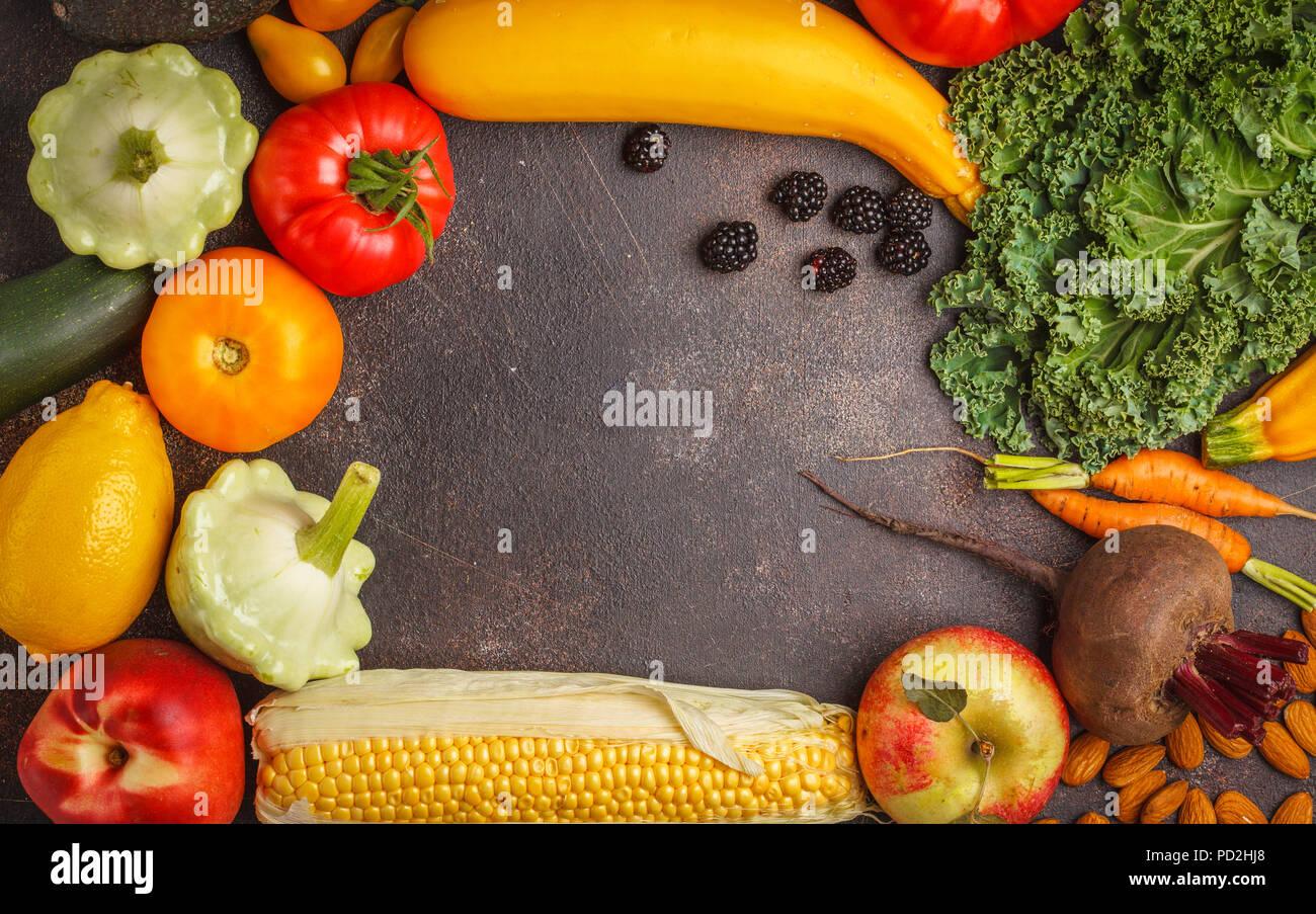 Farbigen Obst, Gemüse und Beeren auf einem dunklen Hintergrund. Saubere Konzept Essen, veganes Essen Hintergrund. Stockbild