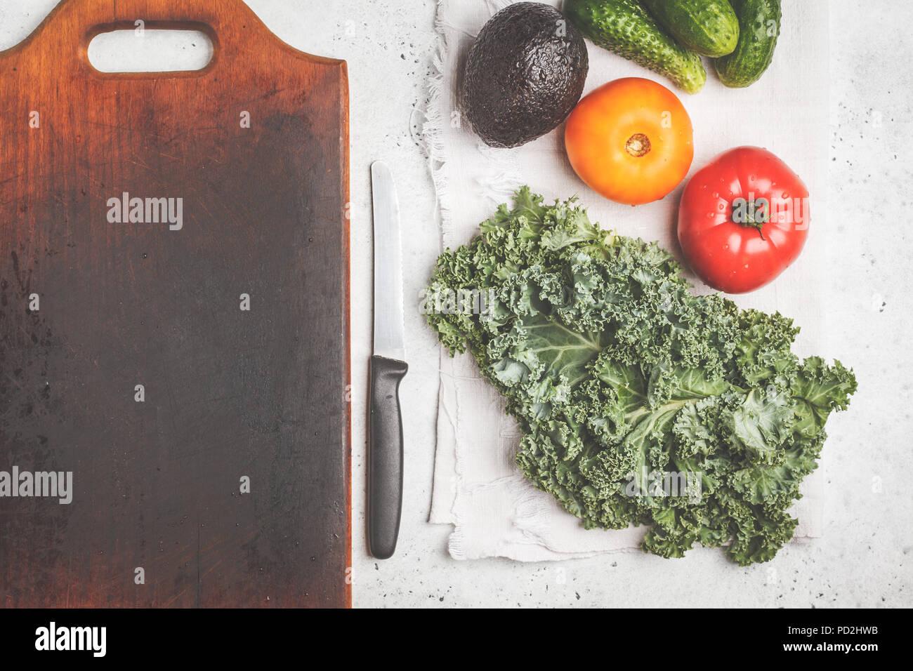 Zutaten für einen gesunden Salat auf einem weißen Tisch, Ansicht von oben. Kochen von Gemüse Salat aus Tomaten, Gurken, Avocado und Kale. Gesunde vegane Ernährung Stockbild