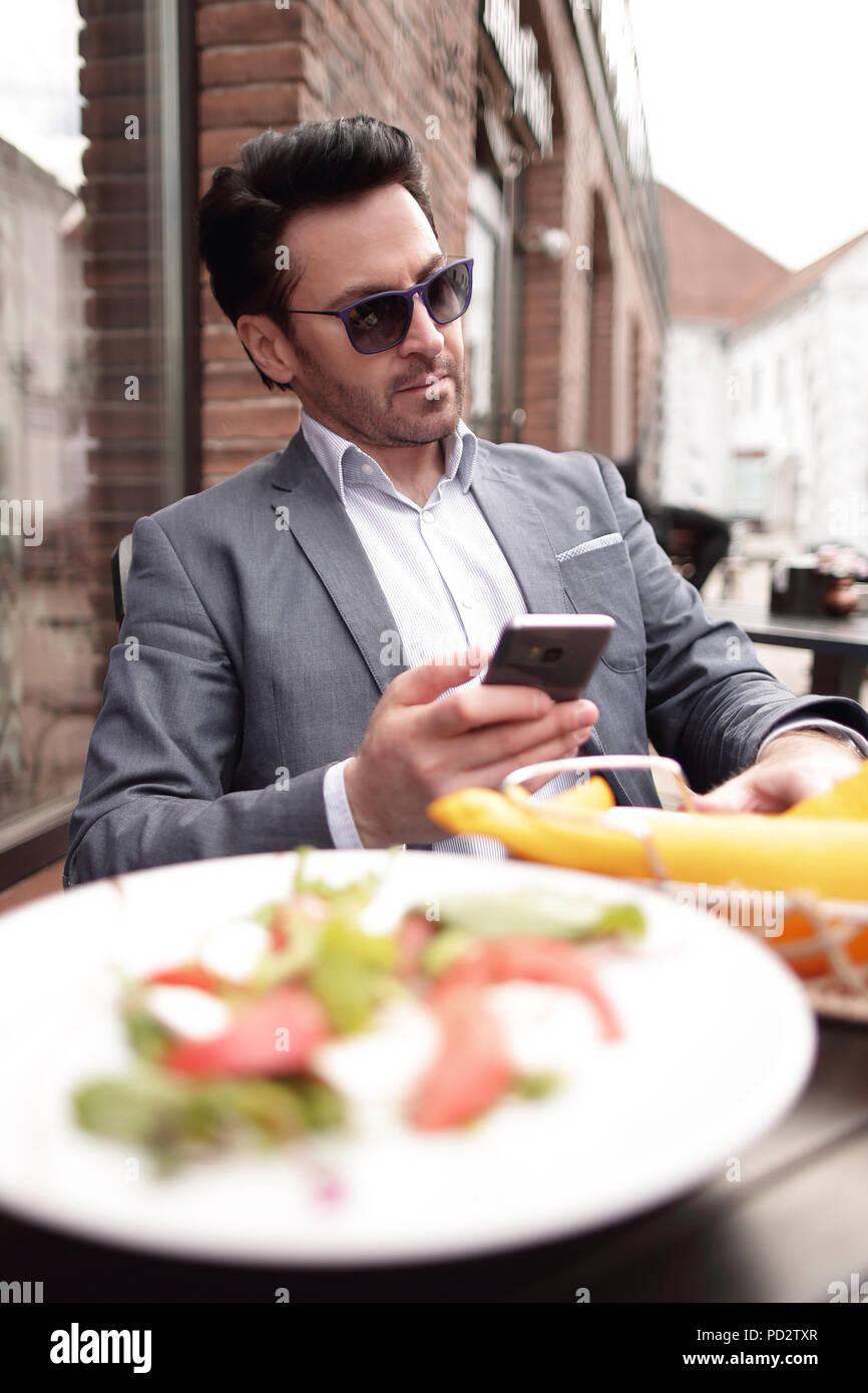 Geschäftsmann in einem Straßencafe sitzen Stockbild