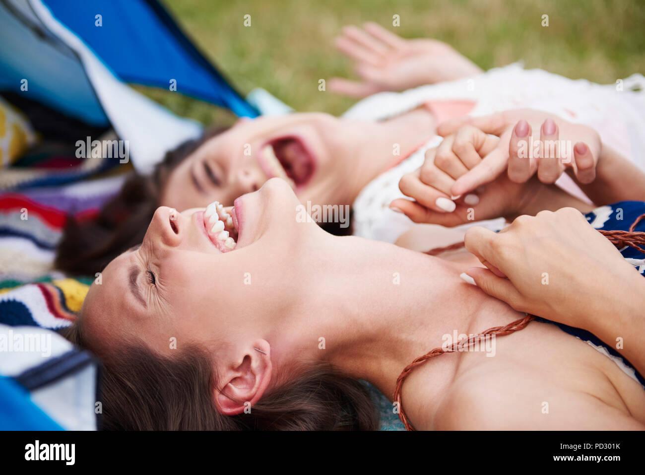 Freunde auf dem Boden liegend, Lachen und Genießen Musik Festival Stockbild