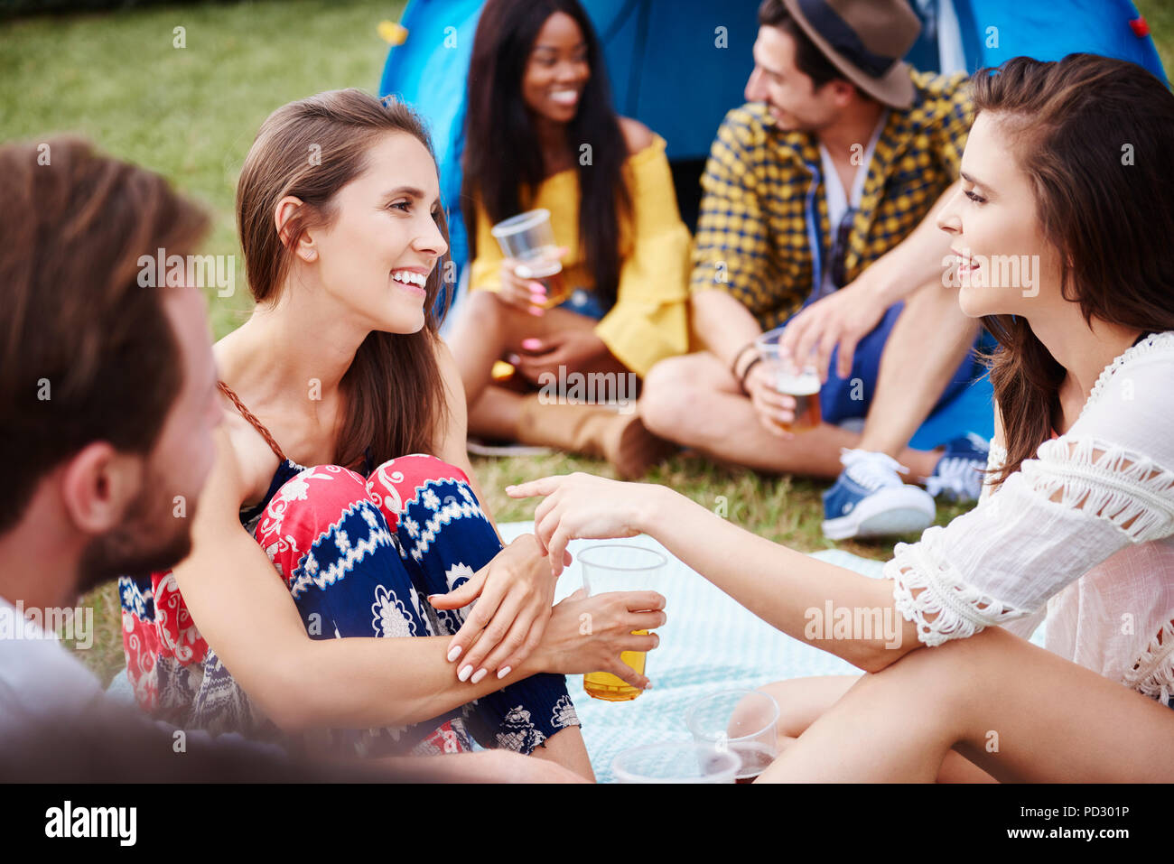 Freunde sitzen und genießen Musik Festival Stockbild