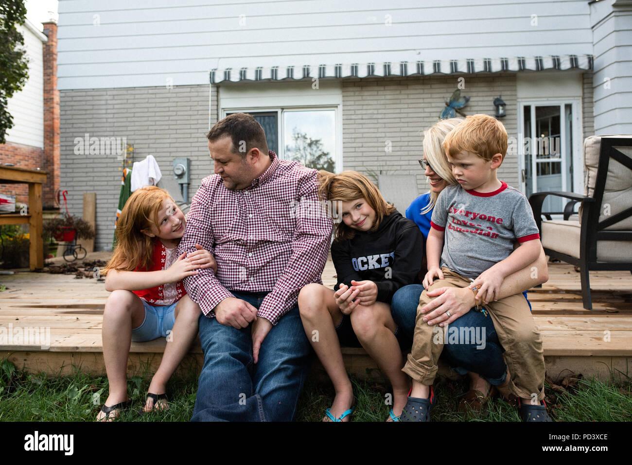 5-köpfige Familie auf der Gartenterrasse Stockbild