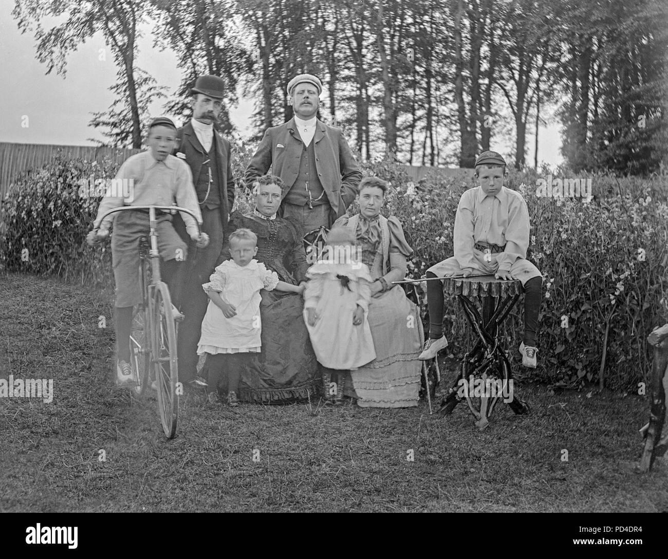 Alate Victorian Foto von einer Familie für die Kamera posieren, irgendwo in England. Es gibt zwei Männer und ihre Frauen, zwei junge Kinder, und zwei Jungen. Einer der Jungen sitzt auf einem Fahrrad von der Zeit. Stockbild