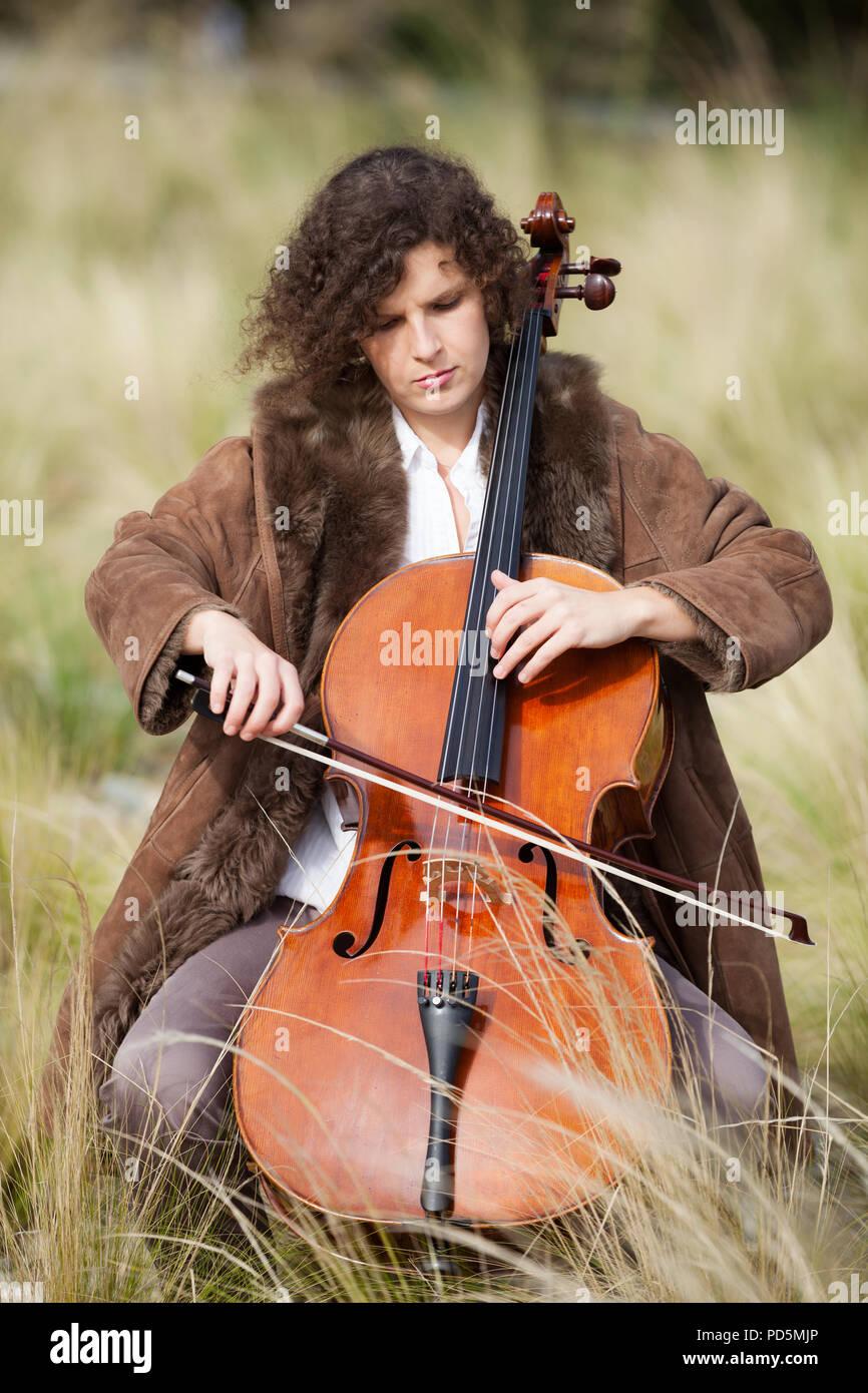 Frau spielt das Cello zwischen Feldern Stockfoto