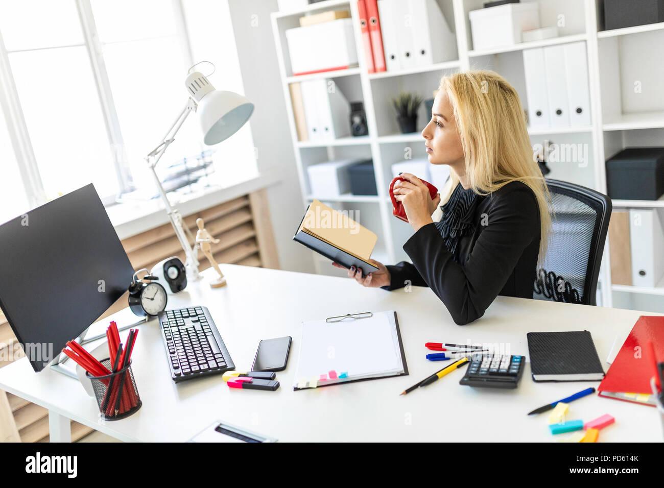 Ein junges Mädchen sitzt an einem Tisch im Büro, eine Schale und ein Buch lesen. Stockbild