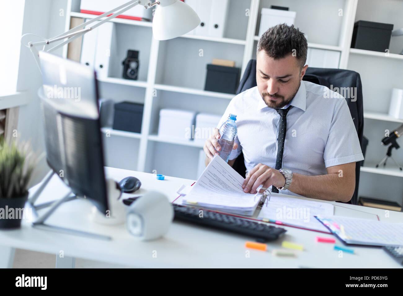 Ein Mann sitzt an einem Tisch im Büro, Arbeiten mit Dokumenten und hält eine Flasche Wasser in der Hand. Stockbild