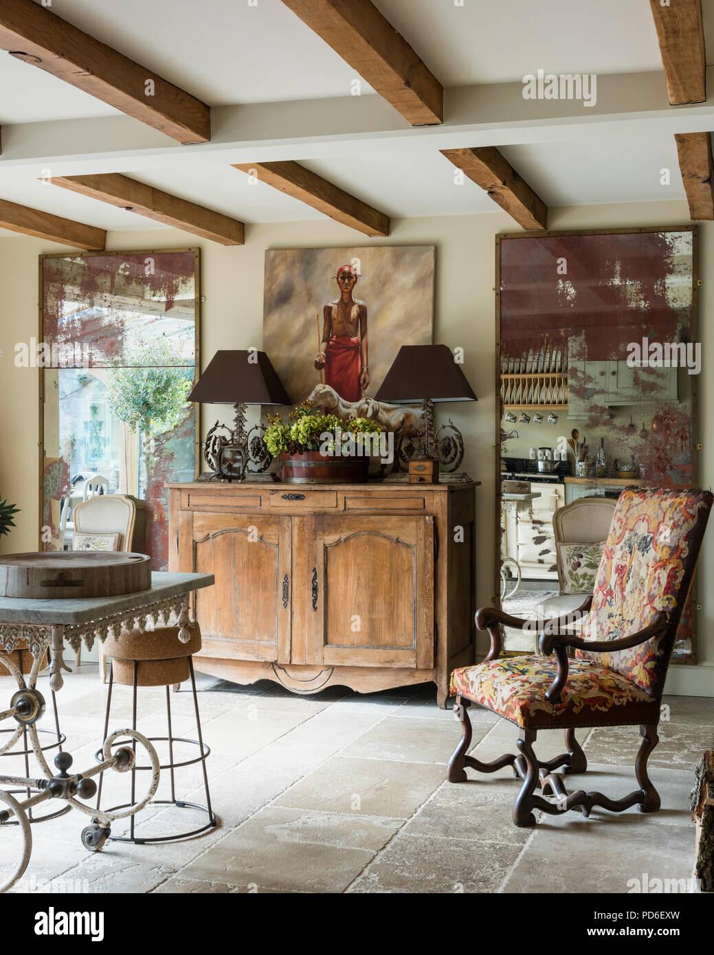 Antiker Stuhl mit distressed Spiegel und Holz- Sideboard mit Lampen. Stockbild