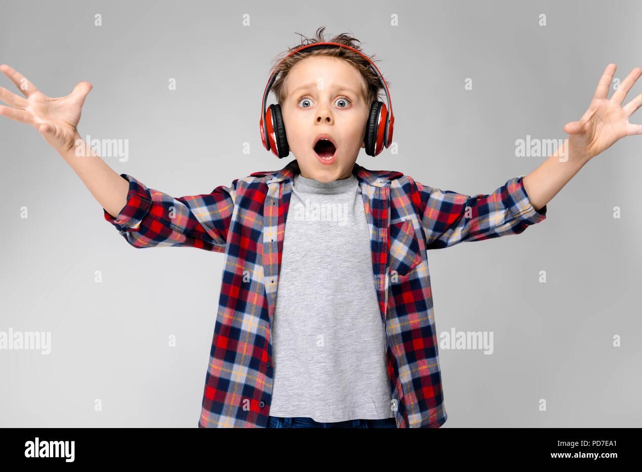 Ein schöner Junge in einem Plaid Shirt, grau Shirt und Jeans steht auf einem grauen Hintergrund. Ein Junge in rot Kopfhörer. Der junge zieht seine Hände nach vorne. Stockbild