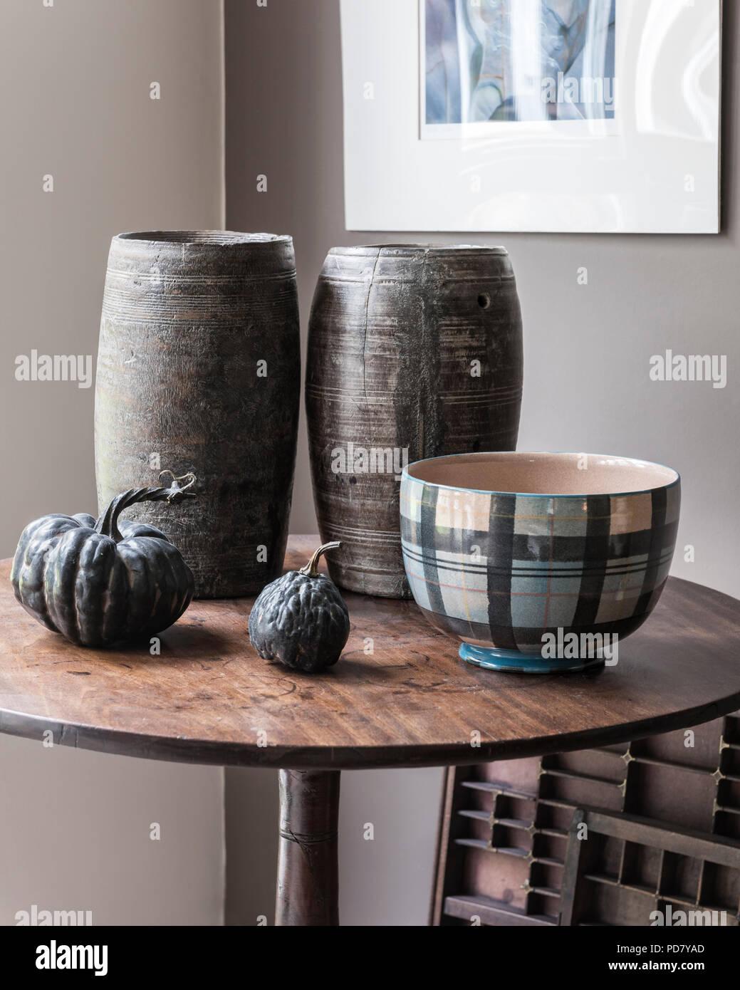 Zwei Holz- Töpfe aus Südafrika sind auf einem kleinen Tisch im Wohnzimmer mit getrockneten Kürbisse und eine Schale aus Anta angezeigt. Stockfoto