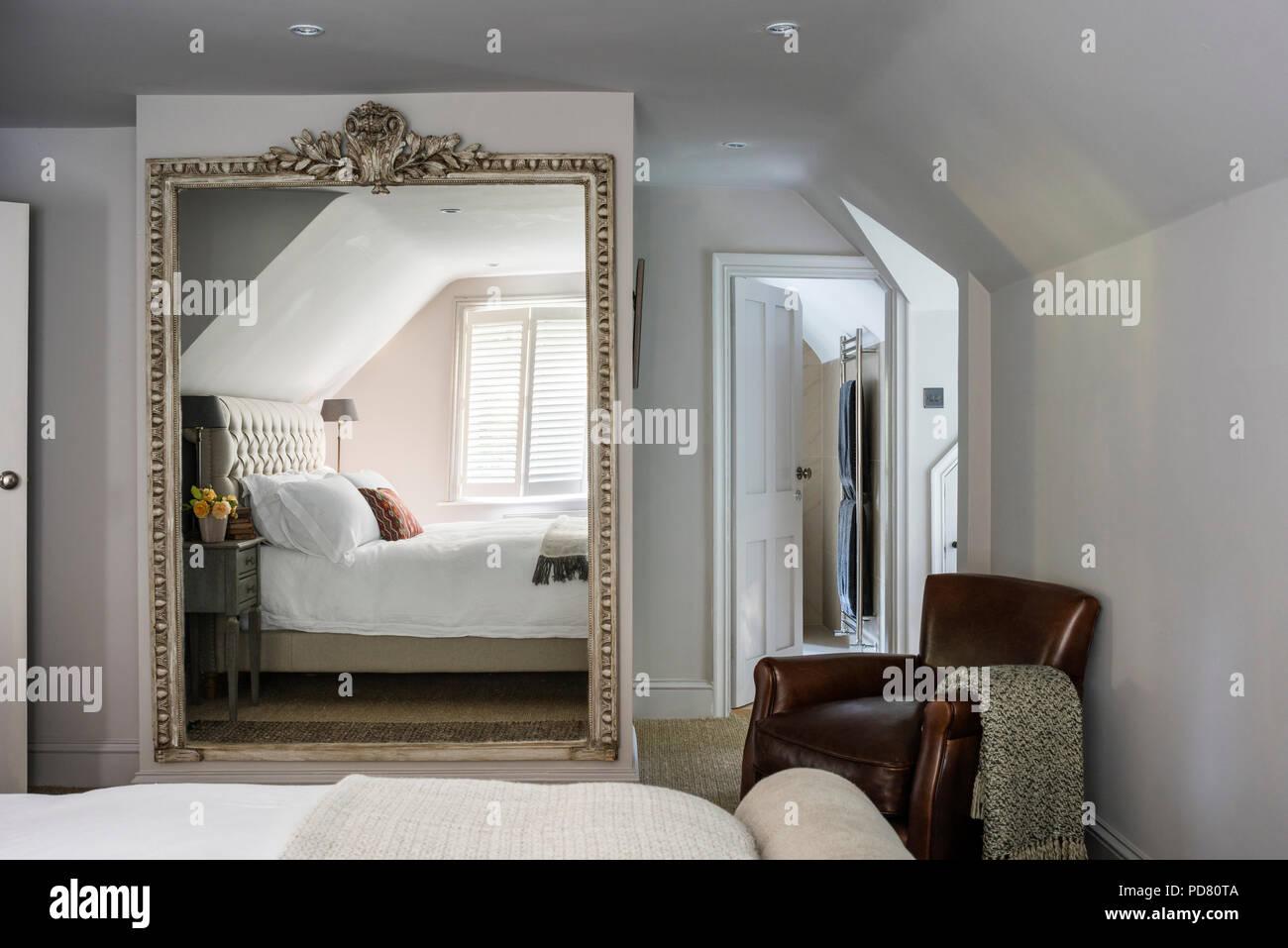 Ledersessel und übergroßer Spiegel im Schlafzimmer mit Pentlow ...