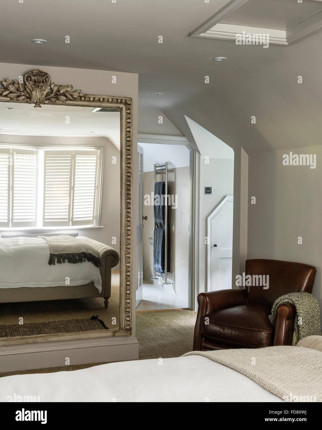 Ledersessel und übergroßer Spiegel im Schlafzimmer mit ...