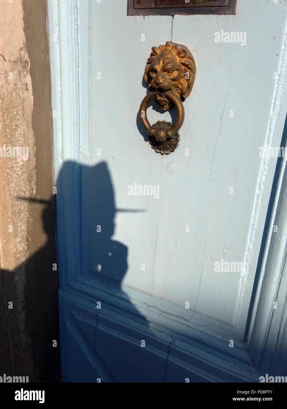 Finstere Mann fotografiert in hat mit einer starken silhouette Schatten auf eine alte französische Tür Stockbild