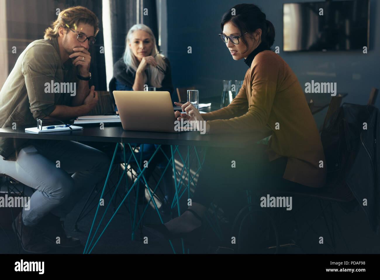 Drei Personen sitzen um einen Tisch und Laptop. Business Frau, Projekt Analyse auf Laptop mit Kollegen. Stockfoto