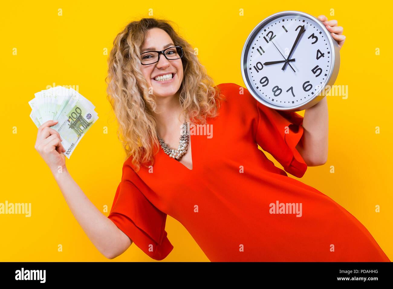 Frau im Kleid mit Uhren und Fan von Banknoten Stockfoto