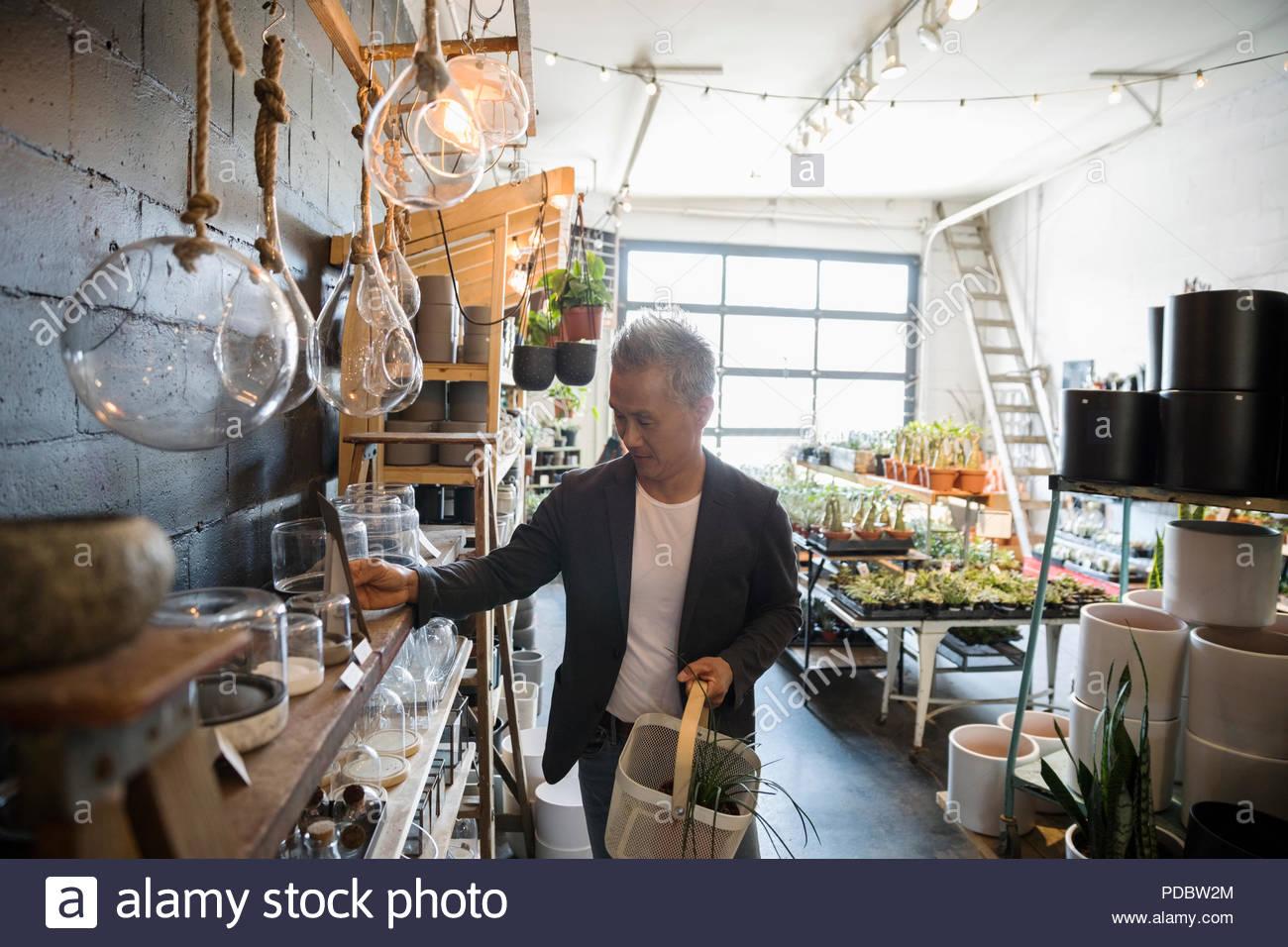 Reifer mann Einkaufen in Pflanzen shop Stockbild