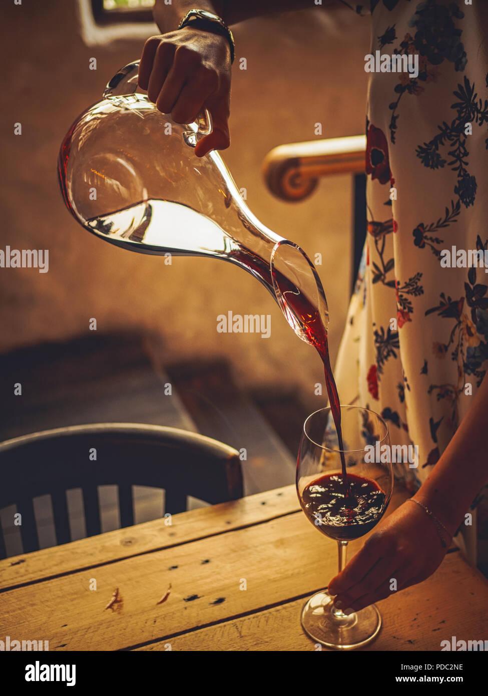 7/8 Schuß von Frau gießen armenischen Wein in Glas Stockbild