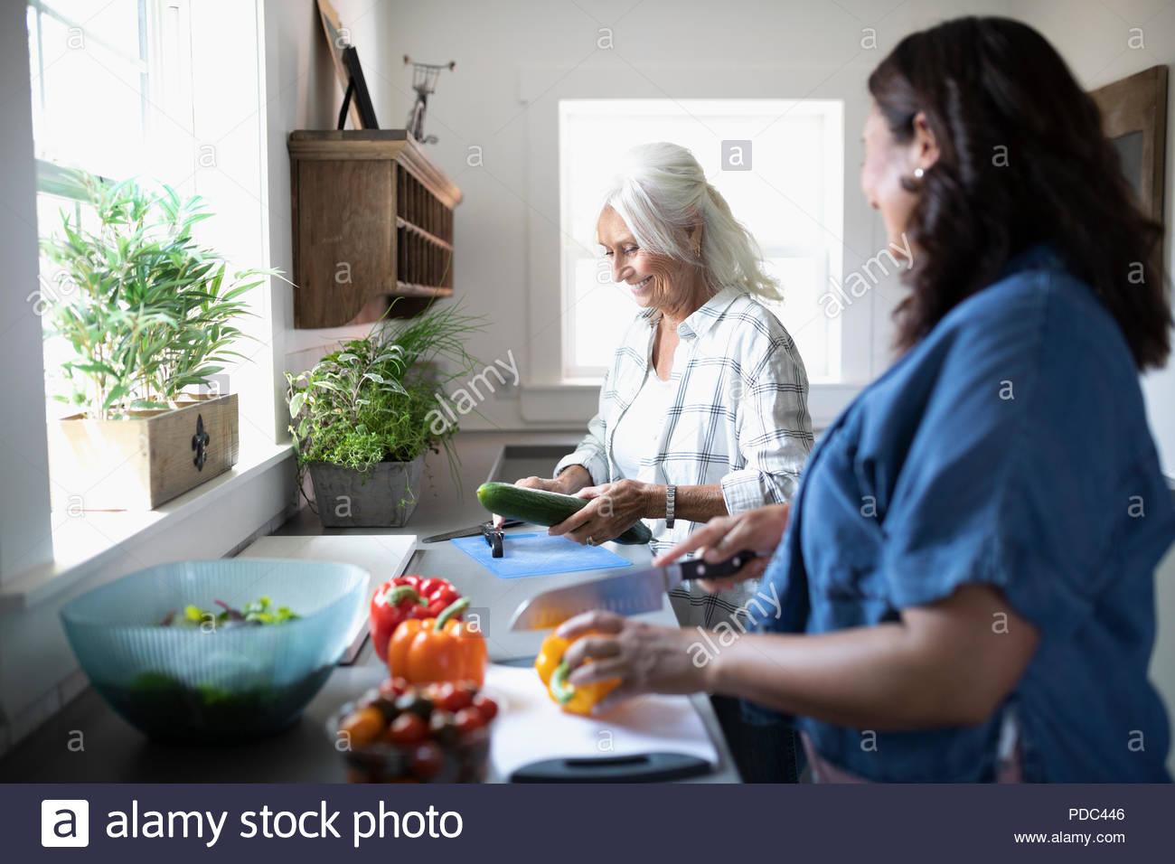 Tochter und Mutter kochen, Schneiden von Gemüse in der Küche Stockbild