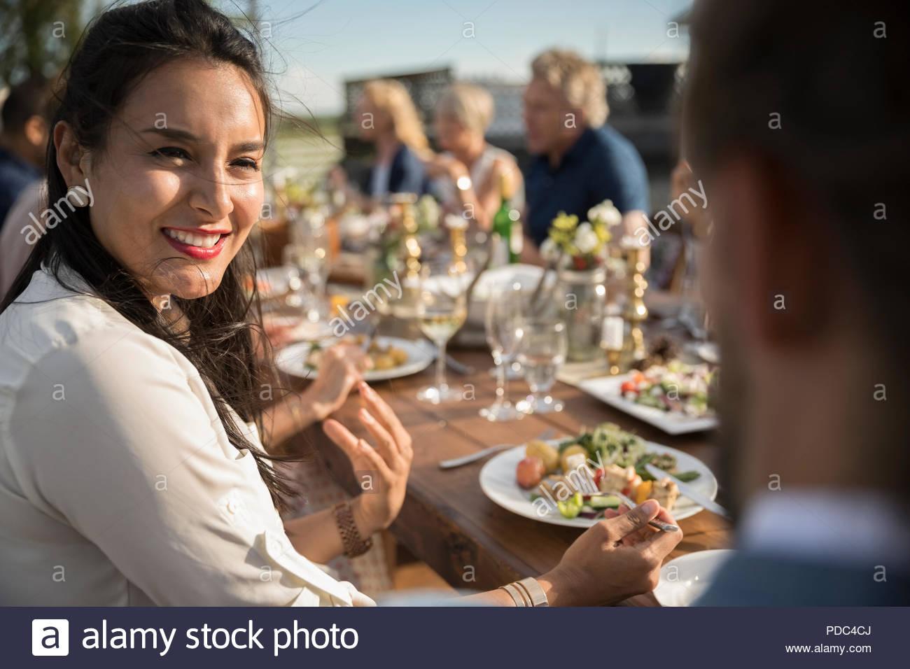 Lächelnde Frau, Essen und Sprechen mit Freund bei Sunny Garden Party Mittagessen Stockbild