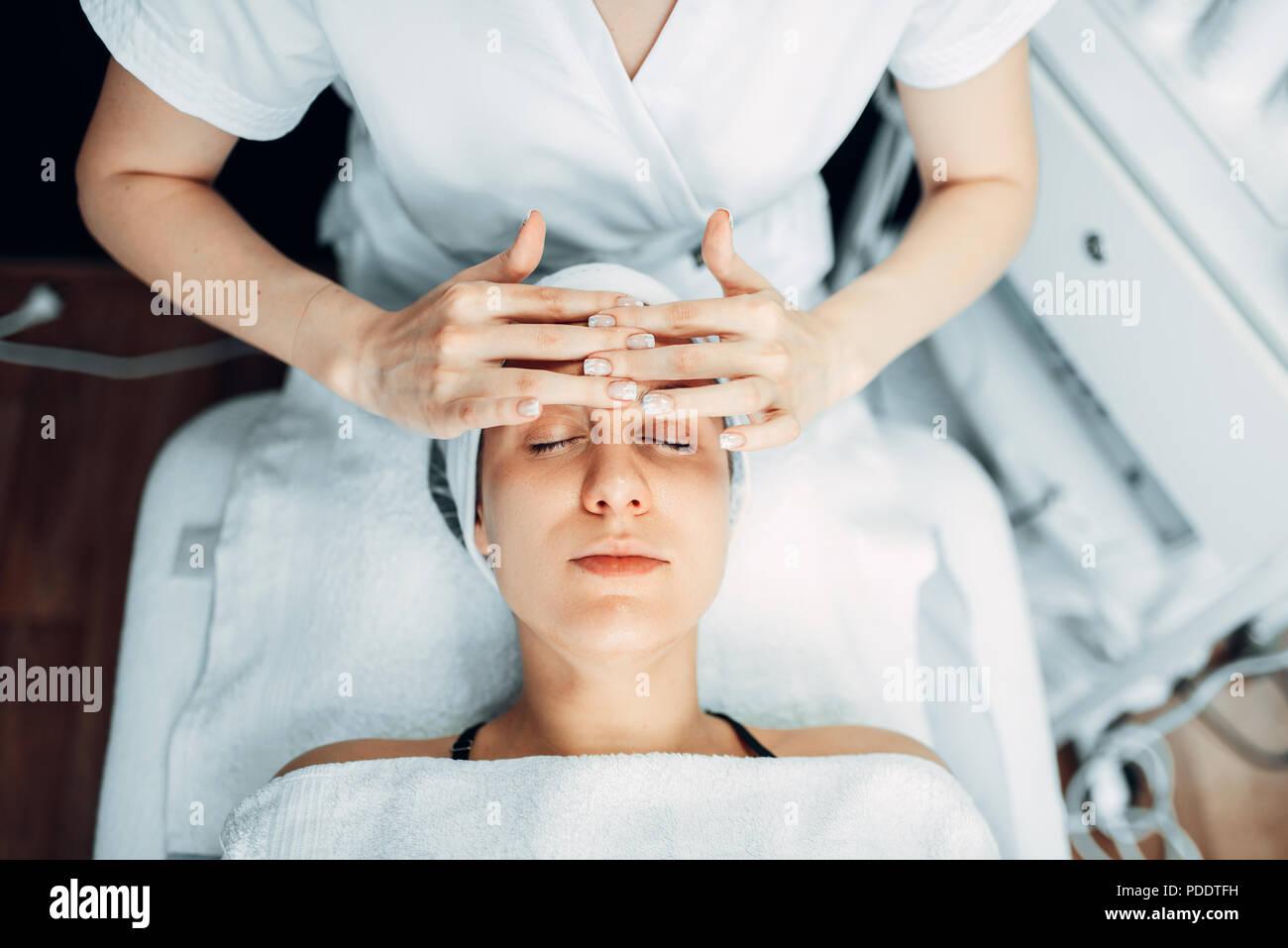 Kosmetikerin reibt die Creme auf die weiblichen Patienten Stockbild