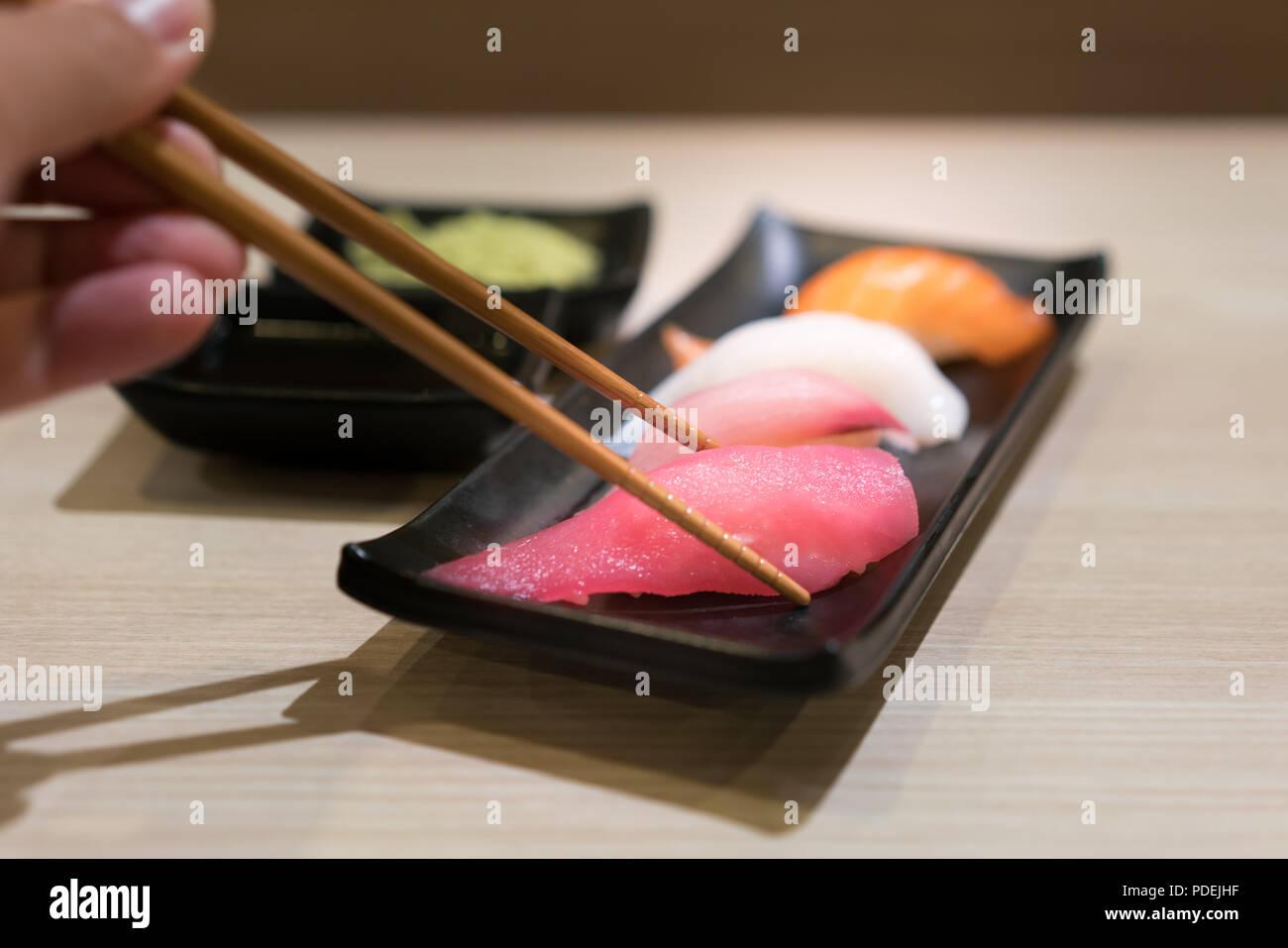 Stäbchen mit Japan rohen Thunfisch Sushi und frische Mischung Sushi in schwarz Platte - Japanisches Essen set Style im japanischen Restaurant. Stockbild