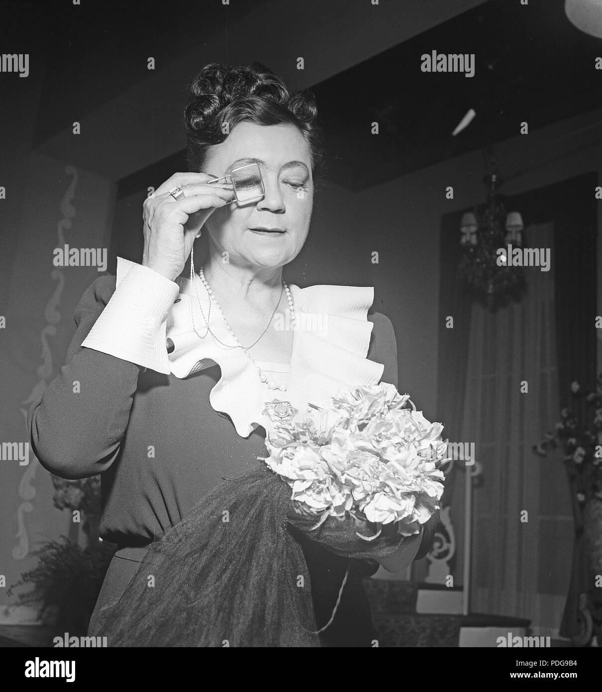 1940 s Frau mit Brille. Eine ältere Dame schaut sich etwas durch ein monokel. Foto Kristoffersson/K 96-5 Stockbild