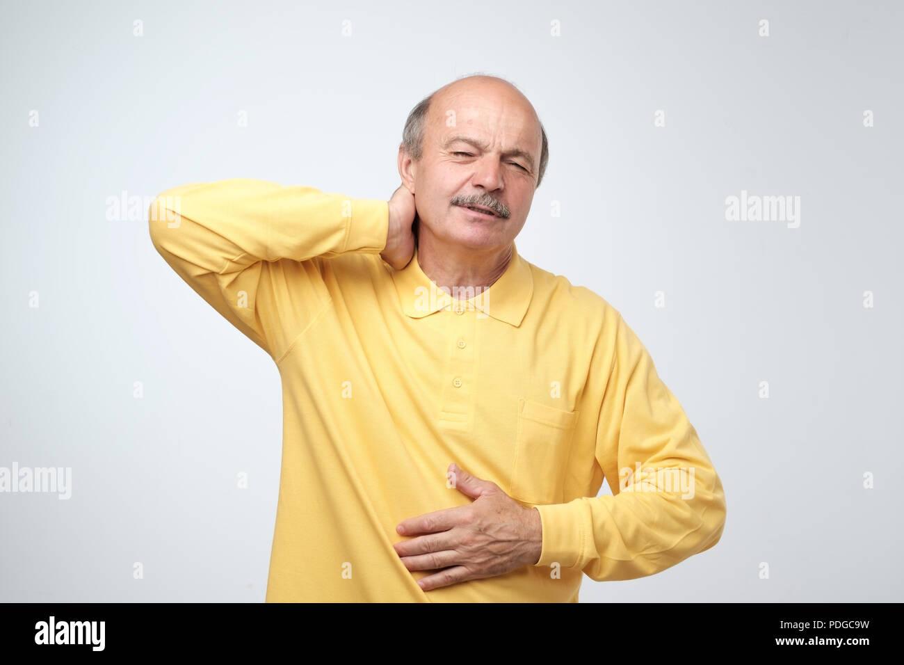 Nahaufnahme von reifer Mann im gelben T-Shirt mit geschlossenen Augen seinen Hals berühren in den Schmerz. Gesundheitliche Probleme im Alter, Neuralgie Konzept Stockfoto
