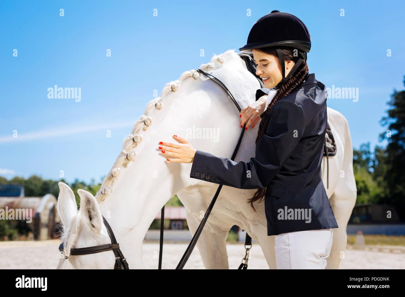 Attraktive weibliche Reiter tragen weiße Hosen und dunklen Jacke Stockbild