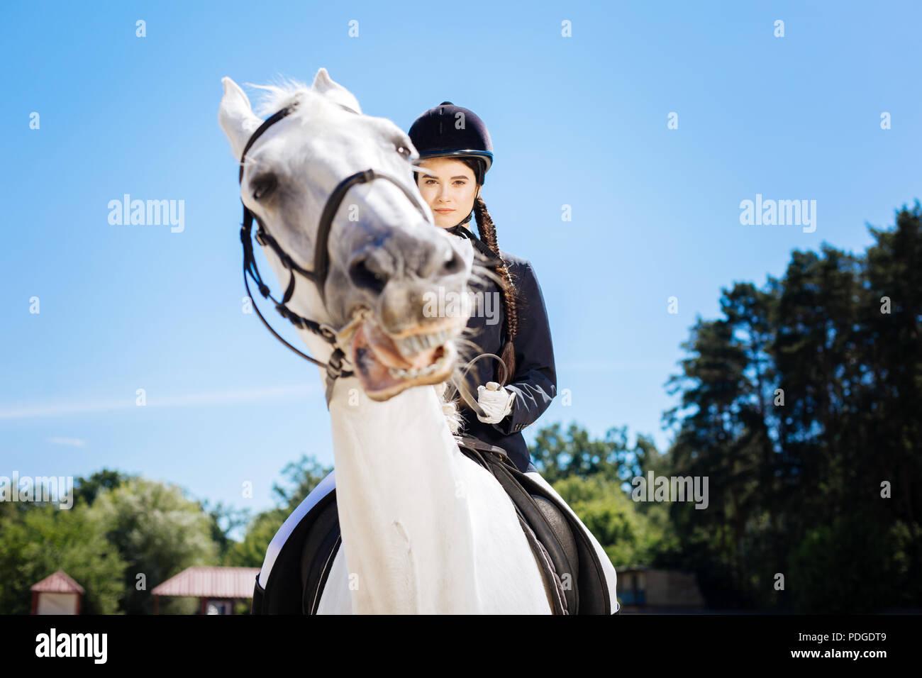 Reiterin mit langen Zopf tragen Helm reiten ihr Pferd Stockbild