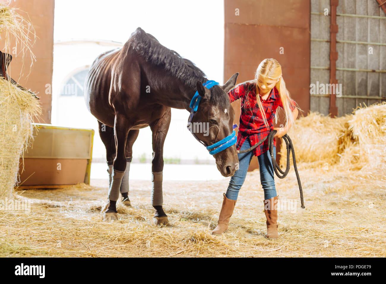 Strahlende Schülerin in Tour in stabilen und führenden Pferd Stockbild