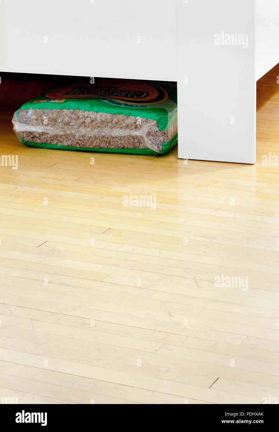 Eine Plastiktüte mit Hamster- oder wüstenrennmaus Bettwäsche aus pflanzlichen Fasern Papier, die sich unter einem Bett gespeichert ist. Stockbild