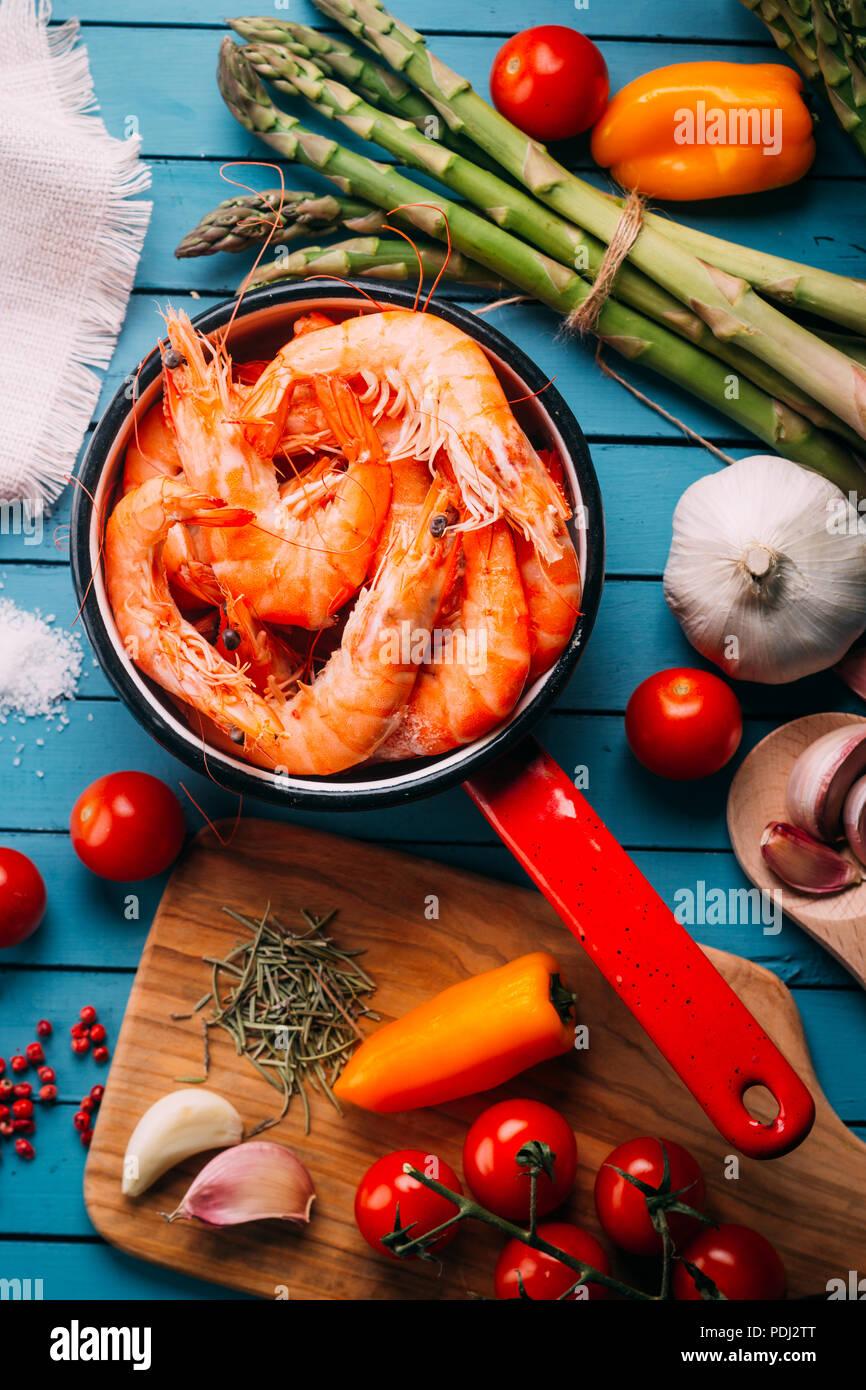 Blick von oben auf die Blaue hölzernen Tisch voll mit Garnelen und einige Zutaten für Gewürze und Gemüse Sie zu mischen, Konzept der Rezepte und Restaurants Stockbild