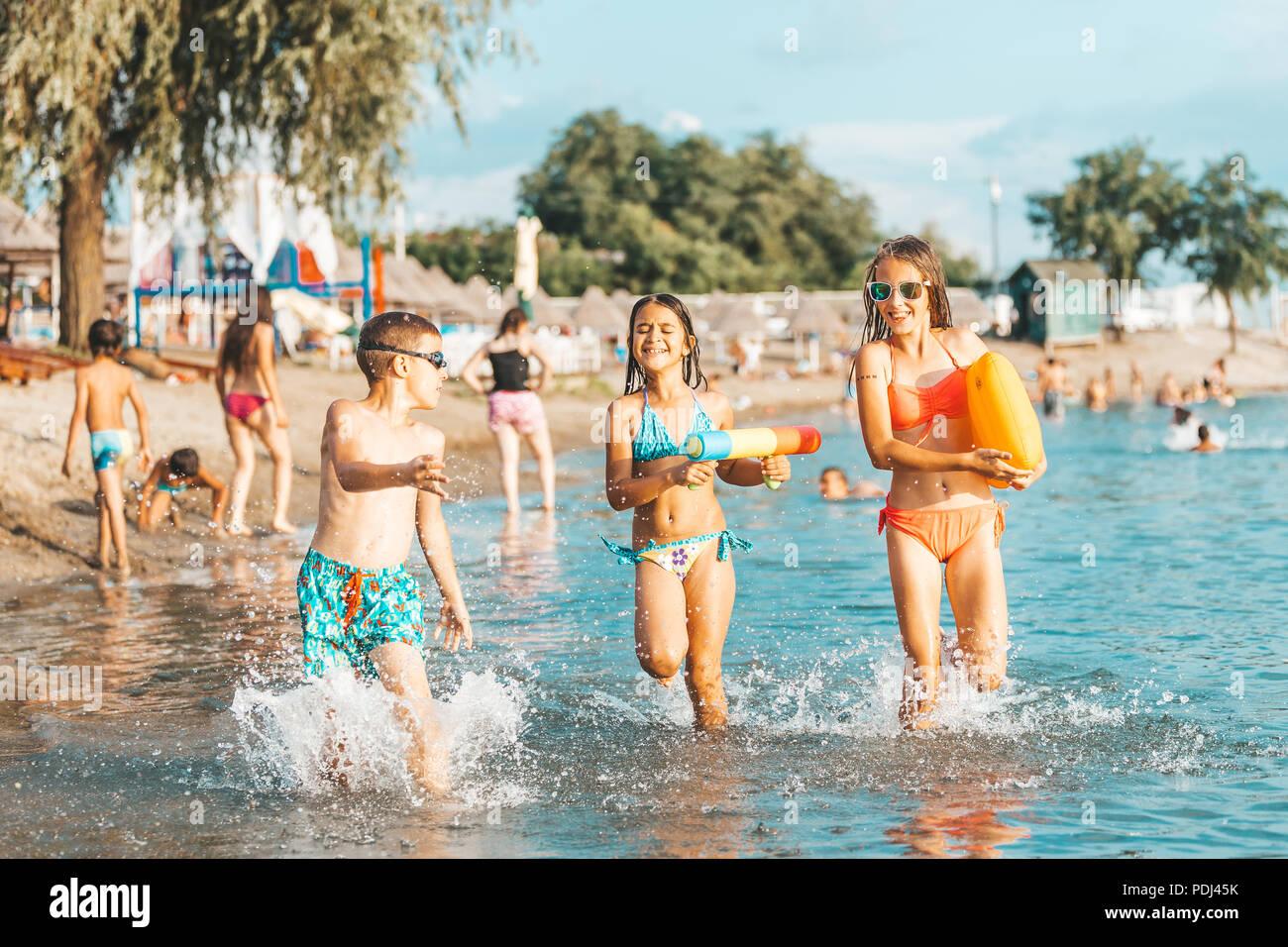 Glückliche Kinder spielen im Meer. Kinder Spaß im Freien. Sommer Urlaub und gesunden Lebensstil Konzept Stockbild