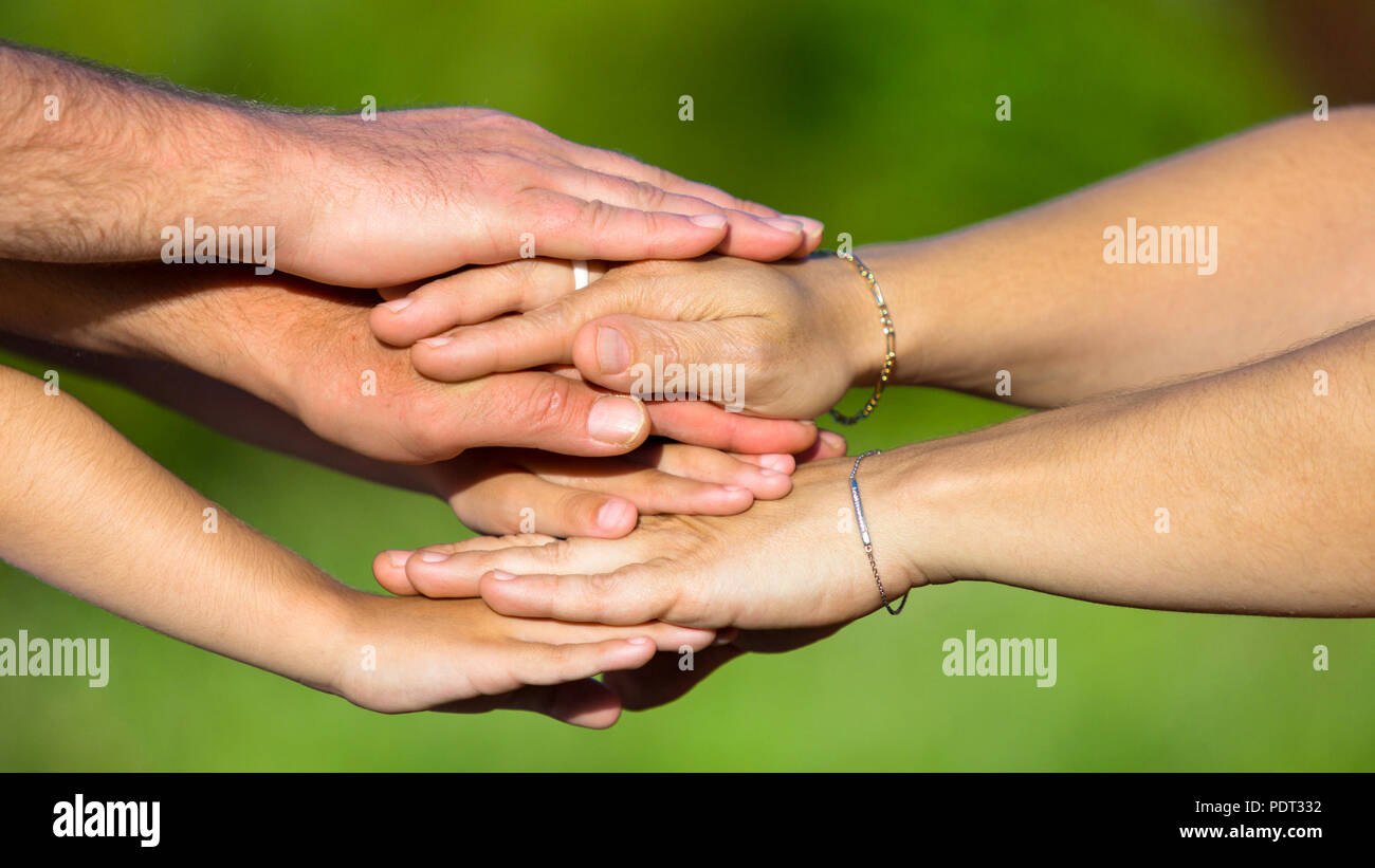 Verschwommen grünen Hintergrund, Männer und womenÕs Hände auf jeder anderen Stockbild