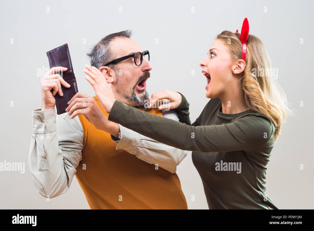 Nerdy Mann versucht, Geld von seiner Frau zu verstecken, weil Sie es allen zu verbringen möchten. Stockbild