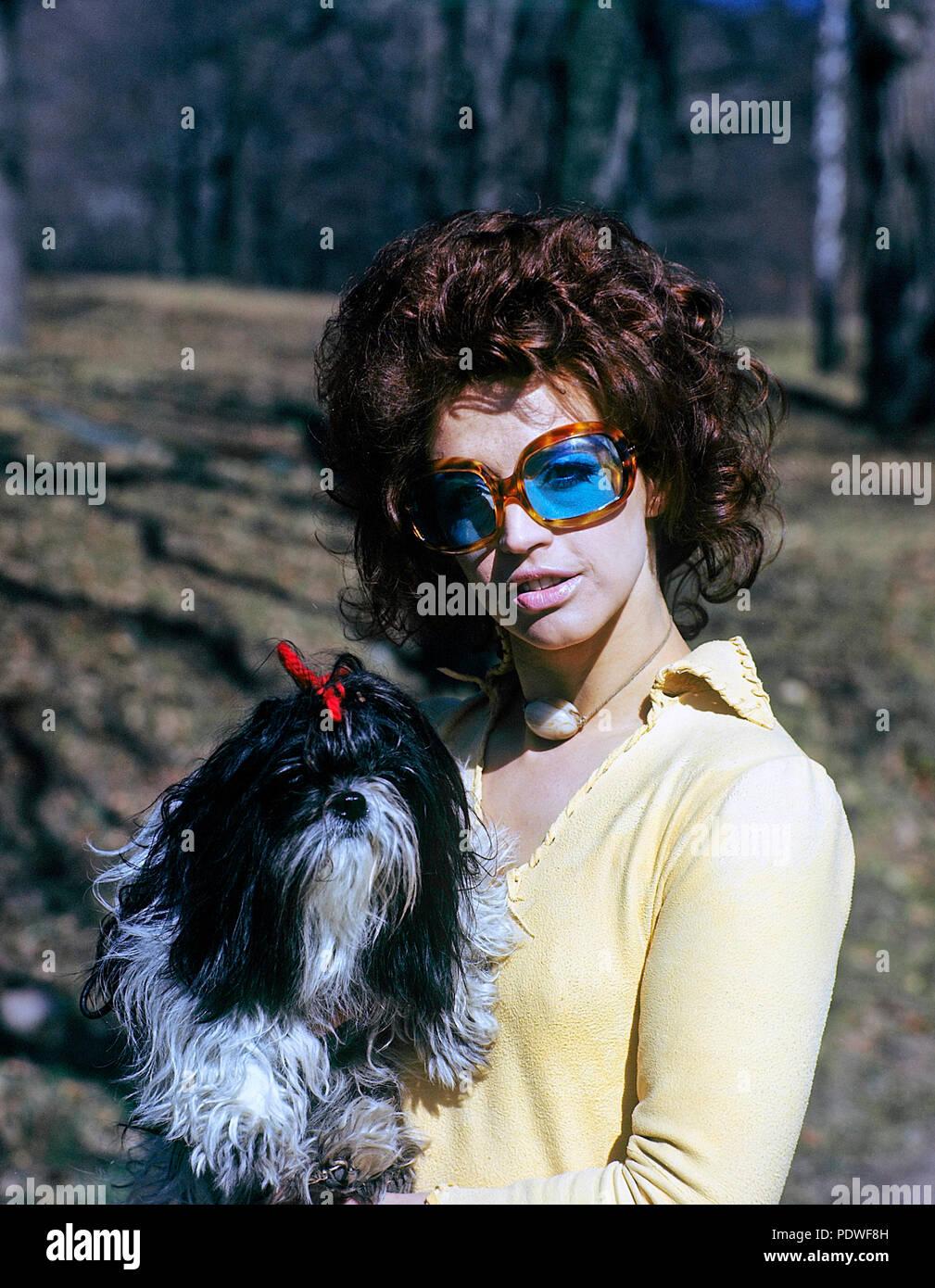 70er Jahre Brille. Eine junge Frau in Blau befleckt Sonnenbrille ist mit ihrem Hund. 1971 Stockbild