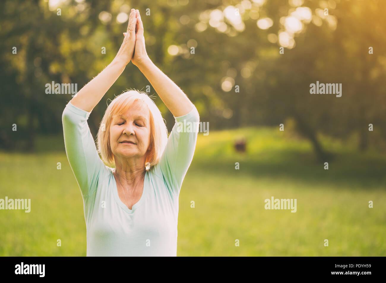 Ältere Frau genießt Meditieren in der Natur. Bild absichtlich abgeschwächt ist. Stockbild