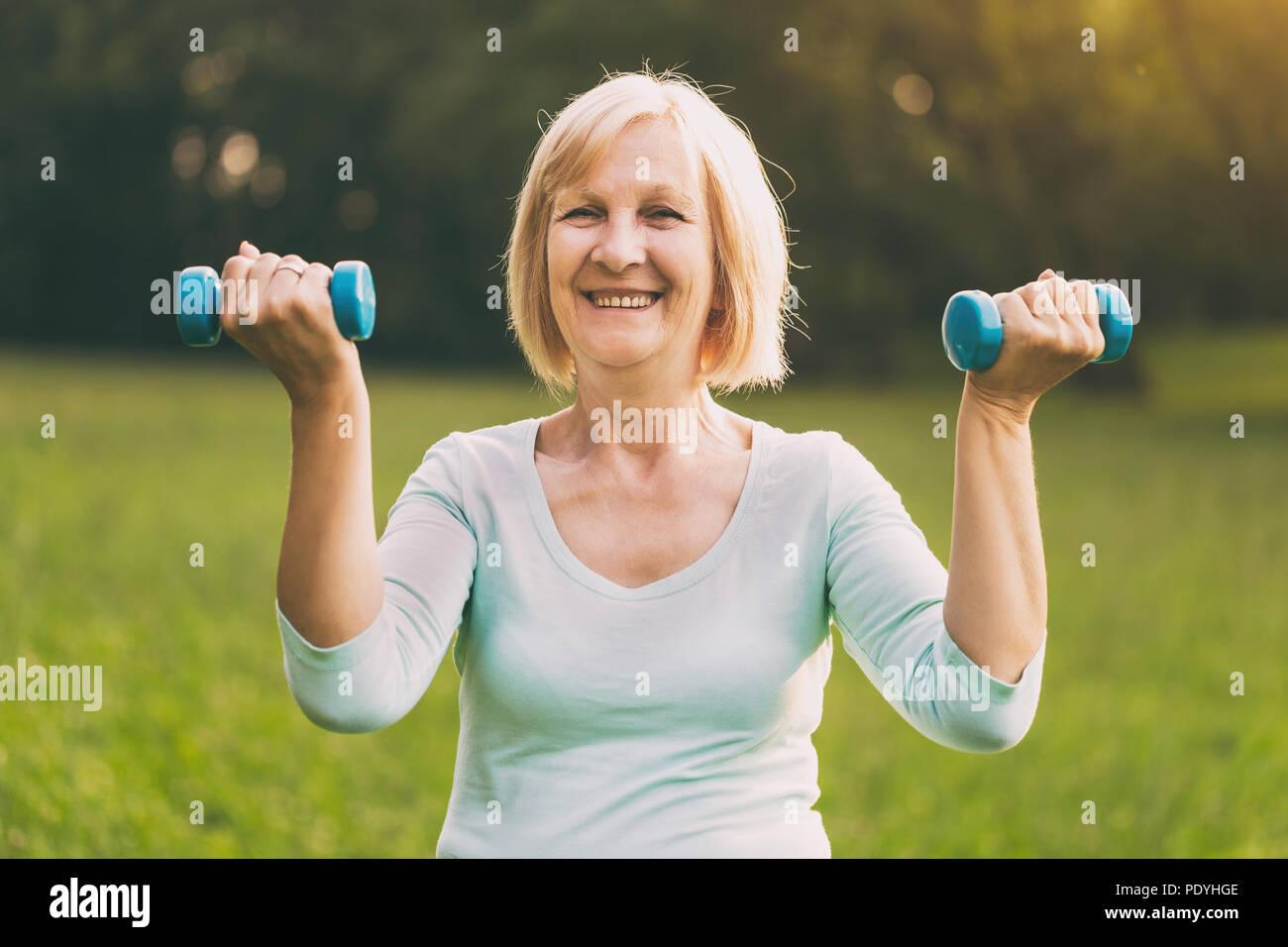 Sportliche ältere Frau Trainieren mit Gewichten outdoor. Bild ist absichtlich abgeschwächt. Stockbild