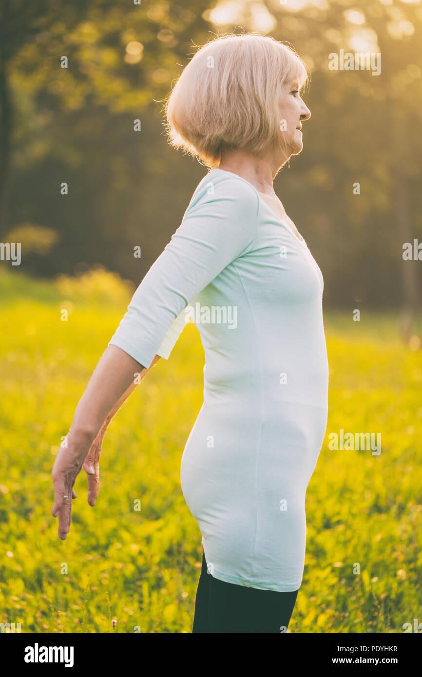 Sportliche ältere Frau Training Outdoor. Bild ist absichtlich abgeschwächt. Stockbild