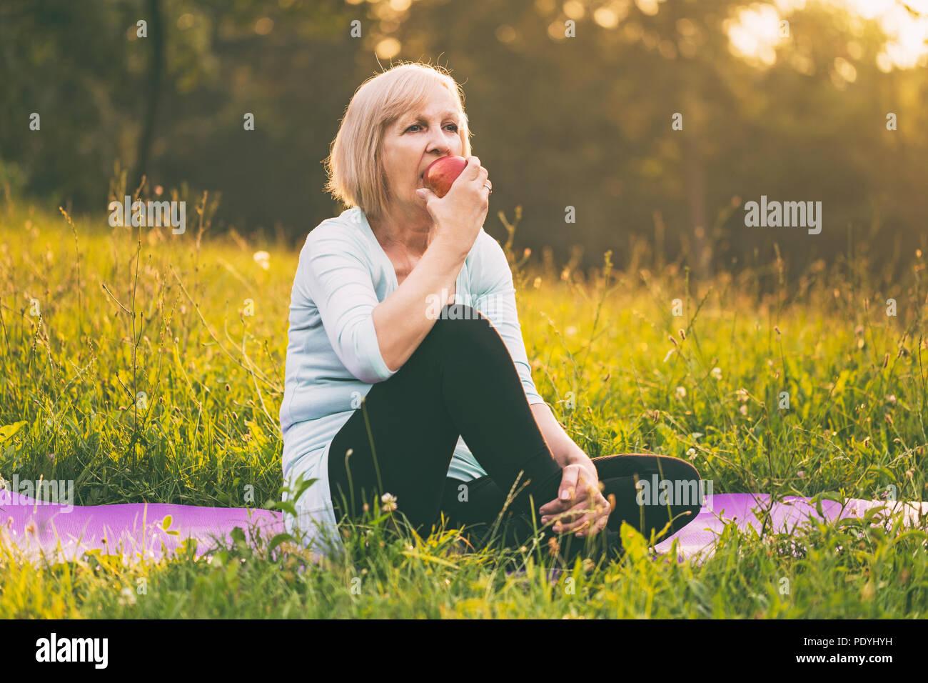 Active Senior Frau essen Apple nach Übung. Bild ist absichtlich abgeschwächt. Stockbild