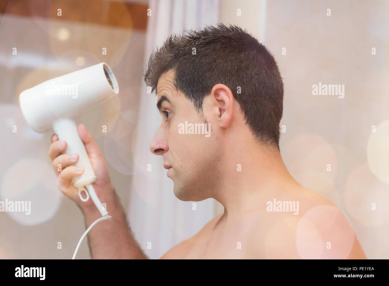 Schöner Mann sein Haar Trocknen mit einem Fön. Konzept Schönheit und Pflege des Menschen Stockbild