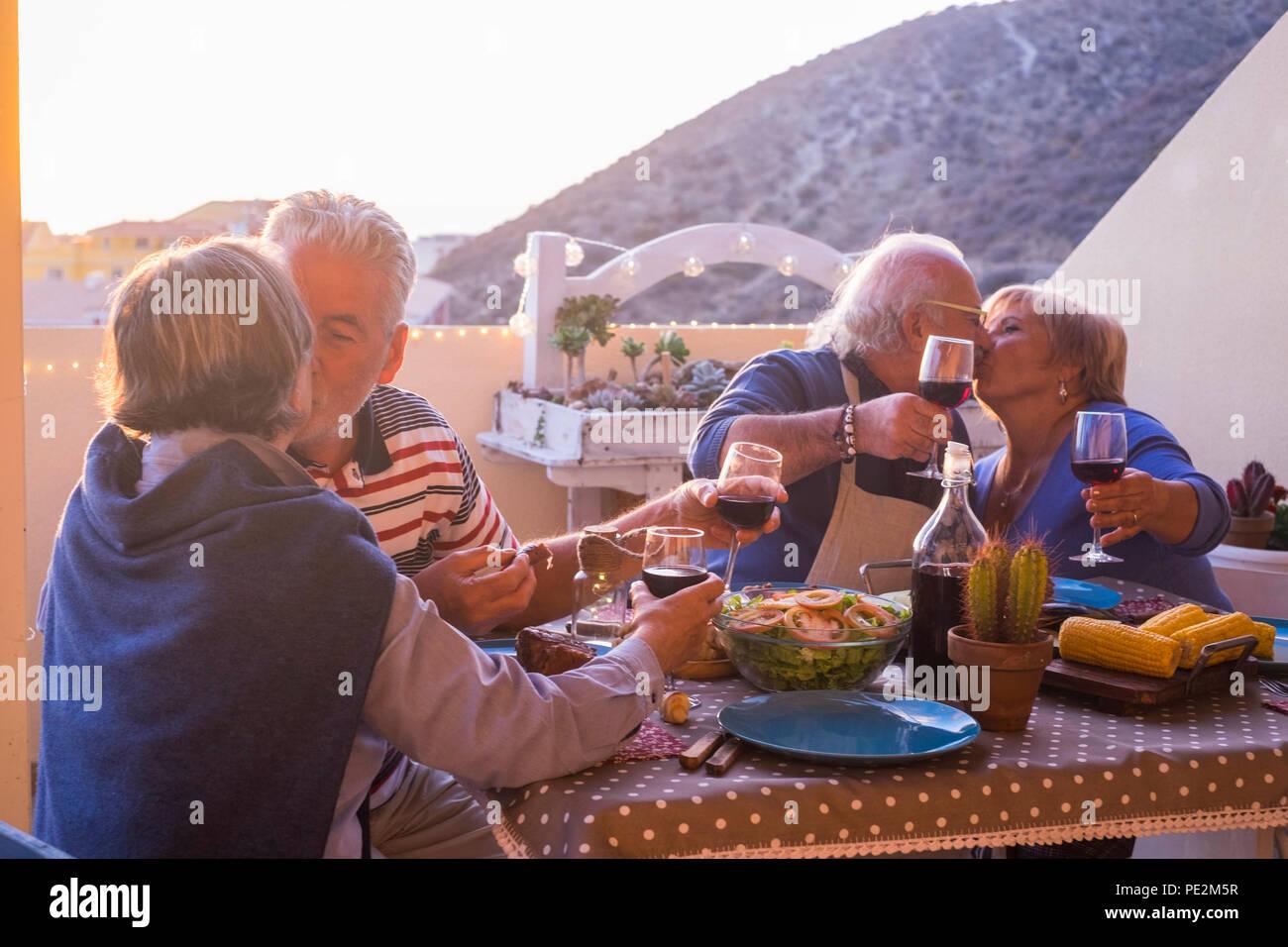 Nette Gruppe der kaukasischen erwachsener Menschen in Glück bleiben zusammen für Abendessen im Freien auf der Terrasse. liebe und freundschaft Konzept mit herrlichen Ausblick. v Stockbild