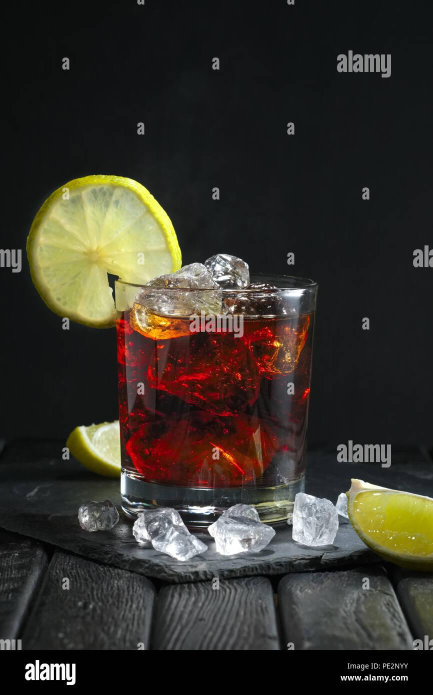 Rum und Cola Cocktail auf dunklem Hintergrund Stockbild