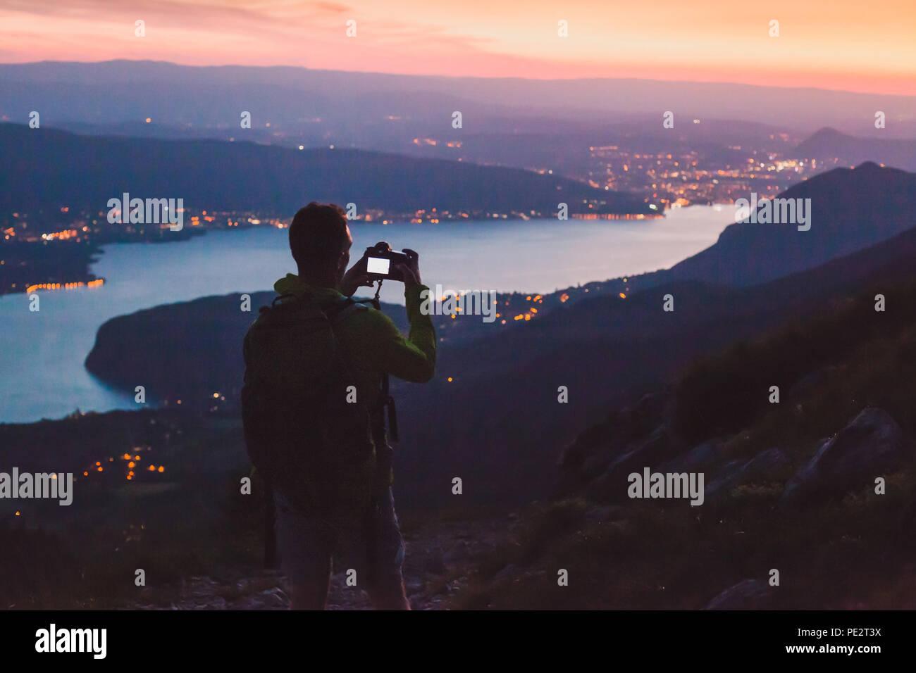 Fotograf, Foto auf DSLR-Kamera am Abend nach Sonnenuntergang Dämmerung, Stadt Panoramablick auf die Berglandschaft low light, Dämmerung Stockbild