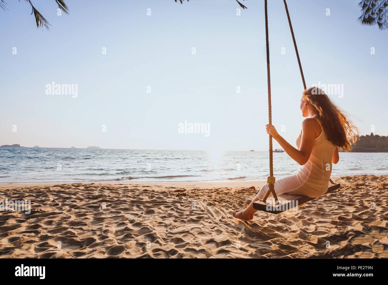 Traum und Glück Konzept, romantische Schöne unbeschwerte Frau entspannend auf der Schaukel im Sunset Beach, Ferien, Urlaub, Reisen und Erholung Stockbild