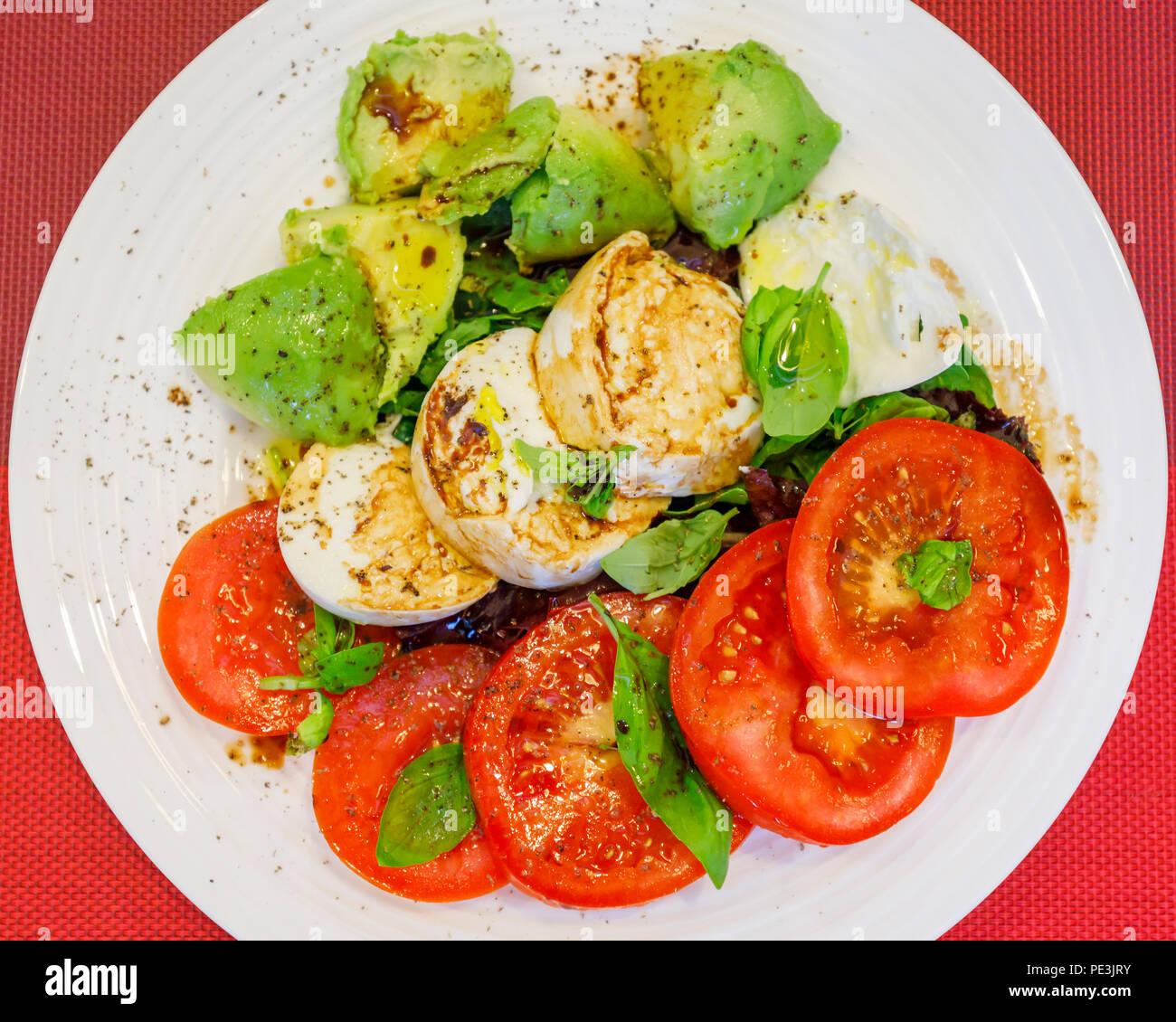 Gesunde Lebensweise: typisch mediterranen Diät, tricolore Salat Zutaten in Scheiben geschnittenen roten Tomaten, White Buffalo Mozzarella und grünen Avocado pear Stockbild