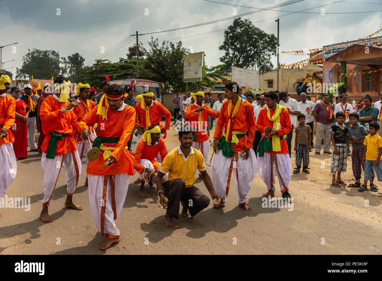 Mellahalli, Karnataka, Indien - November 1, 2013: Karnataka Rajyotsava Parade. Gruppe von orangen und weißen Tänzer und Akrobaten anschickt, in st durchführen Stockbild