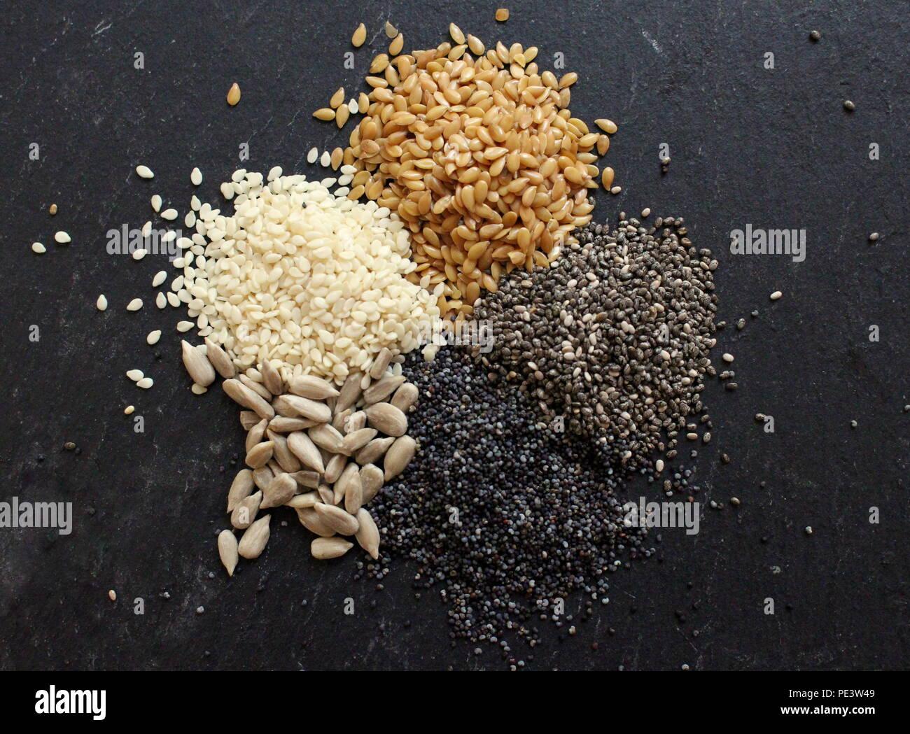 Nahaufnahme von oben nach unten Foto von einer Vielzahl von Samen, einschließlich blauer Mohn, Sesam, Sonnenblumenkerne und Chia Samen Stockbild