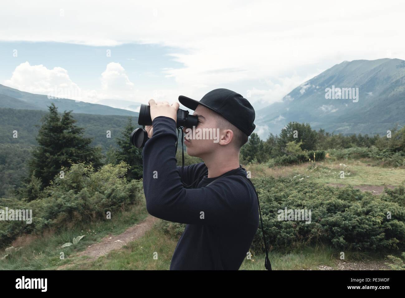 Wanderer blick durch ein fernglas vor der hügel und berge