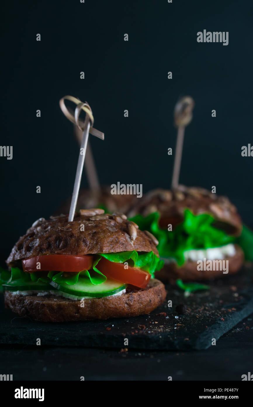 Grüne Sandwich mit Salat, Tomaten, Gurken und Frischkäse auf Beton. Stockfoto