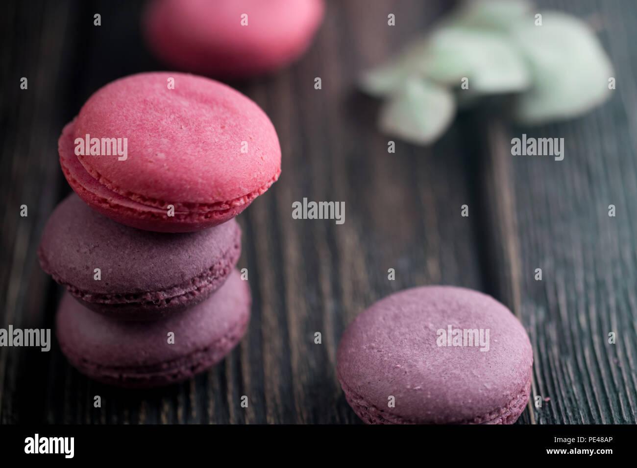 Gruppe der Macarons aus Erdbeeren, Sahne, Schokolade und Heidelbeeren. Rustikale Foto. Getönt. Stockbild
